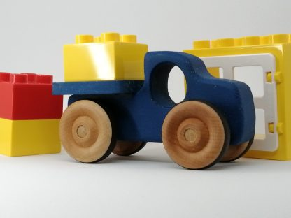 Photo of blue wooden pickup toy with other toys