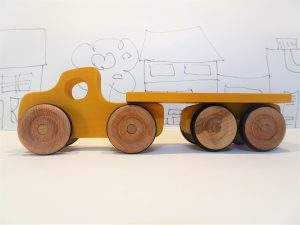 yellow toy wooden lorry and trailer